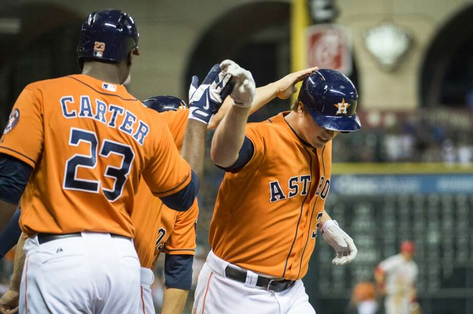 Astros third baseman Matt Dominguez is congratulated by first baseman Chris Carter (23) and designated hitter Brandon Laird after hitting a grand slam. Photo: Smiley N. Pool, Houston Chronicle