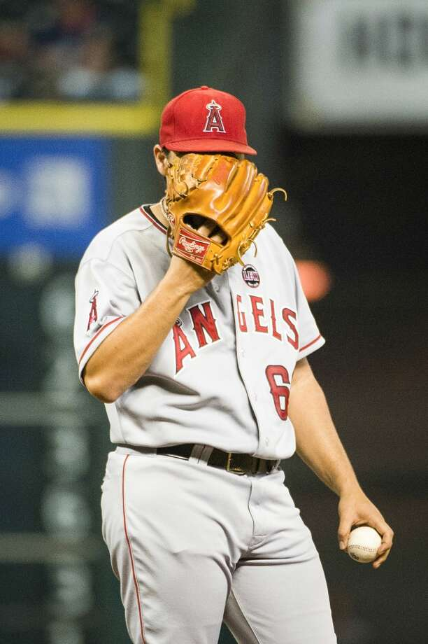 Angels starting pitcher Jason Vargas  buries his face in his glove after giving up a single to Astros second baseman Jose Altuve to load the bases during the fifth inning. Photo: Smiley N. Pool, Houston Chronicle