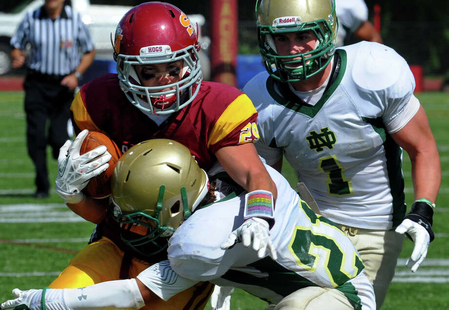 St. Joseph's Lars Pedersen gets tackled by Notre Dame of West Haven's Zachary Cotrancesco, during high school football action in Trumbull, Conn. on Saturday September 14, 2013. Coming in from behind is Salvatore Esposito. Photo: Christian Abraham / Connecticut Post