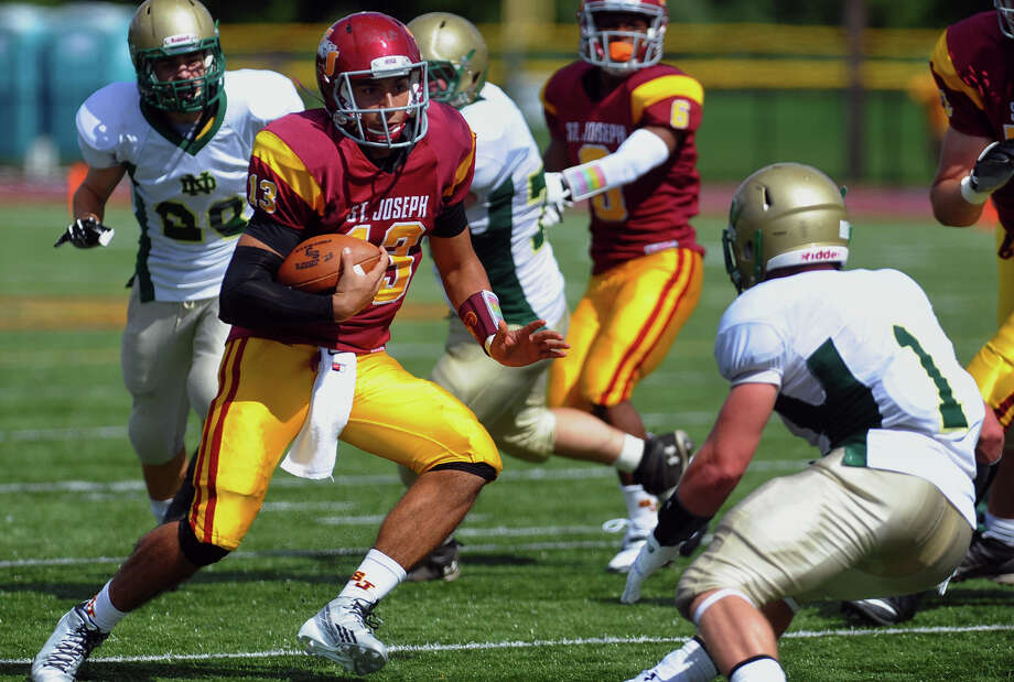 St. Joseph QB Jordan Vazzano tries to avoid a tackle by Notre Dame of West Haven's Salvatore Esposito, during high school football action in Trumbull, Conn. on Saturday September 14, 2013. Photo: Christian Abraham / Connecticut Post