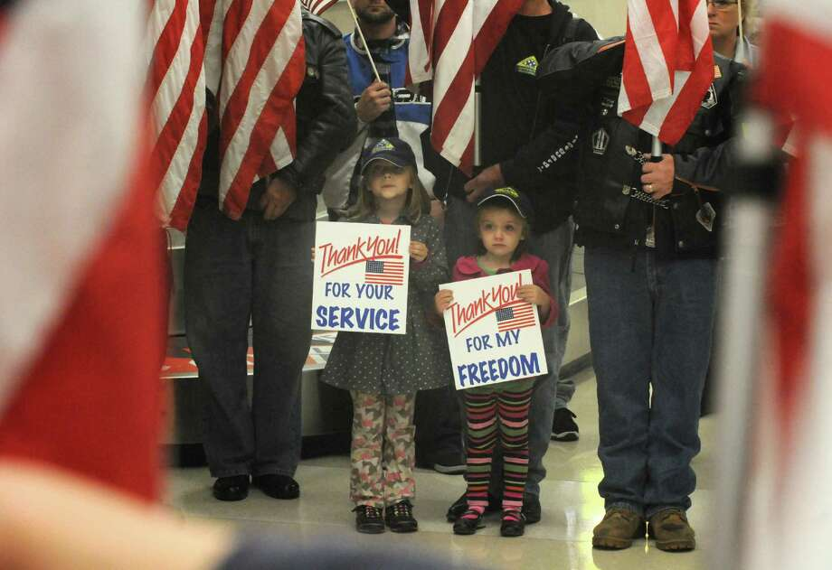 Sisters Kaitlyn Farrow, left (6), and Sydney Farrow, (4), of Troy join the Patriot Guard in welcoming World War II veterens before their Honor Flight at Albany International on Saturday Sept. 14, 2013 in Colonie, N.Y. (Michael P. Farrell/Times Union) Photo: Michael P. Farrell / 00023602A