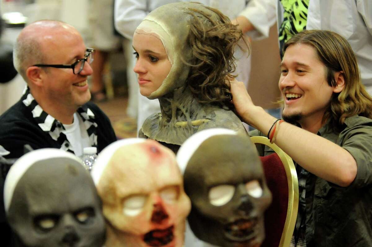 Makeup artist Jared Balog of Troy, right, changes Natalie Cross, 17, of East Greenbush into a Zombie character during FantaCon 2013 on Saturday, Sept. 14, 2013, at the Marriott Hotel in Colonie, N.Y. Shawn Maloy of Albany, left, assists. The comic book, horror and fantasy convention continues Sunday from 10 a.m. to 5 p.m. (Cindy Schultz / Times Union)