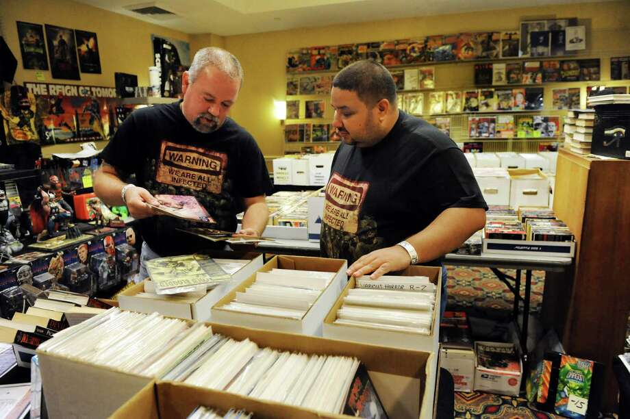 Dealer Baul Bacher of Baltimore, left, helps Robert Cruz of The Bronx with comic book purchases during FantaCon 2013 on Saturday, Sept. 14, 2013, at the Marriott Hotel in Colonie, N.Y. The comic book, horror and fantasy convention continues Sunday from 10 a.m. to 5 p.m. (Cindy Schultz / Times Union) Photo: Cindy Schultz / 00023870A