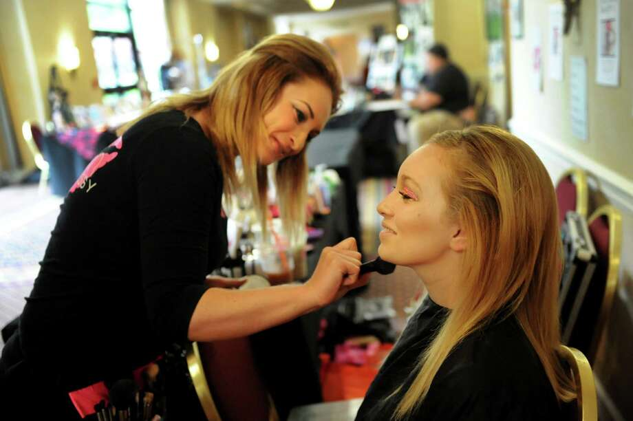 Genn Shaughnessy of Muah Makeup and Hair in Albany, left, applies fairy-inspired makeup on her daughter, Kaliegh Reed, 14, during FantaCon 2013 on Saturday, Sept. 14, 2013, at the Marriott Hotel in Colonie, N.Y. The comic book, horror and fantasy convention continues Sunday from 10 a.m. to 5 p.m. (Cindy Schultz / Times Union) Photo: Cindy Schultz / 00023870A