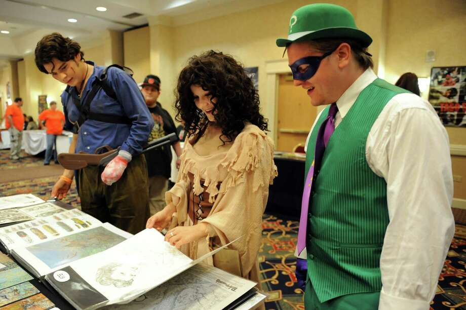 "Michael Gilbert, left, and Stephanie Ward, center, both of Burnt Hills and dressed as characters from the ""Evil Dead"" series, join Ben McCauley of Albany, who portrays the Riddler from ""Batman,"" look at artwork during FantaCon 2013 on Saturday, Sept. 14, 2013, at the Marriott Hotel in Colonie, N.Y. The comic book, horror and fantasy convention continues Sunday from 10 a.m. to 5 p.m. (Cindy Schultz / Times Union) Photo: Cindy Schultz / 00023870A"