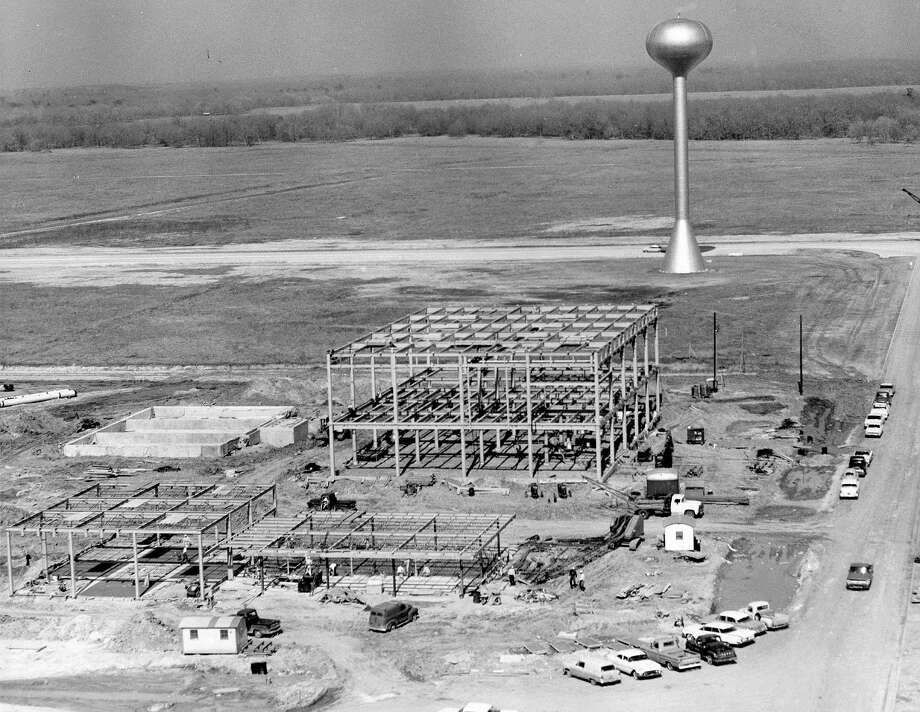 After months of expensive damage and site preparation work at the Clear Lake site of the Manned Spacecraft Center, the buildings are, at last, going up. The water tower marks the center of the site which is expected to have a daily working population of 10,000 persons by the end of 1965. At left foreground is the steel framework for the firehouse. Between it and the water tower is the framework for the central heating and cooling plant. The foundation for the cooling tower may be seen near the plant structure. Photo: Owen Johnson, Houston Chronicle / Houston Chronicle