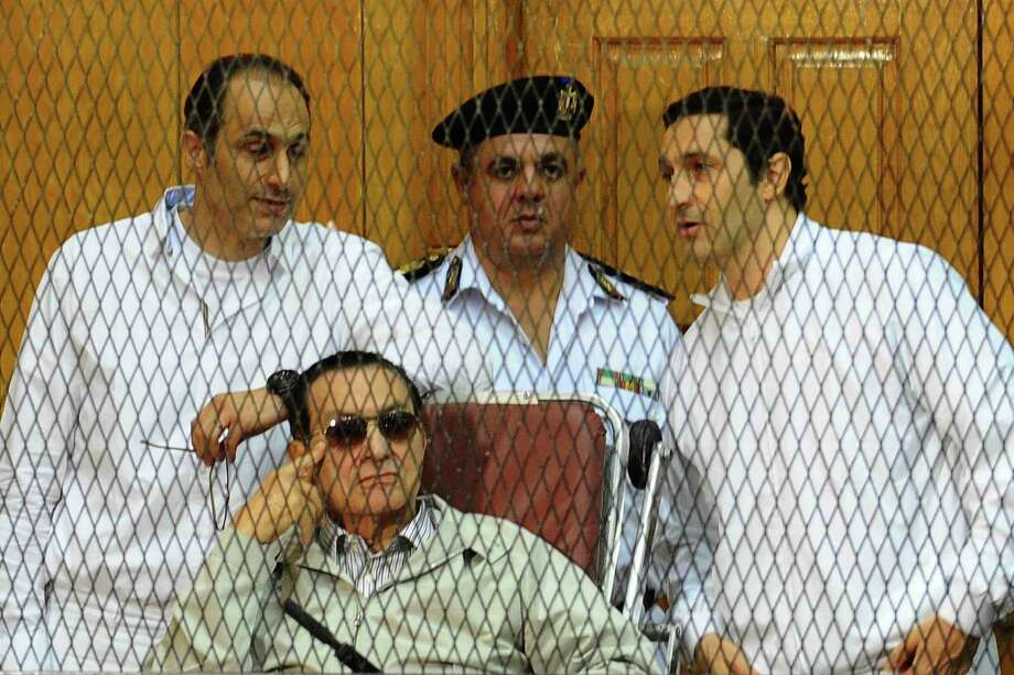 Ousted former President Hosni Mubarak (seated) and his sons Alaa (right) and Gamal stand behind bars during their trial in Cairo. Photo: AFP/Getty Images