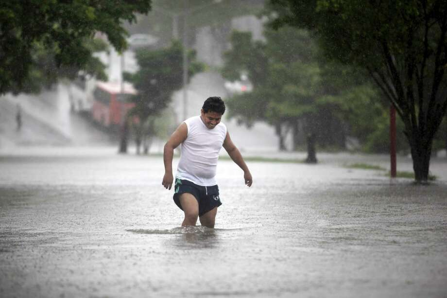 A man walks through a floodwaters in Veracruz, Mexico, Friday during heavy rains caused by Tropical Storm Ingrid. Ingrid threatens more damage where landslides and flooding have killed dozens of people in recent weeks. Photo: Felix Marquez / Associated Press