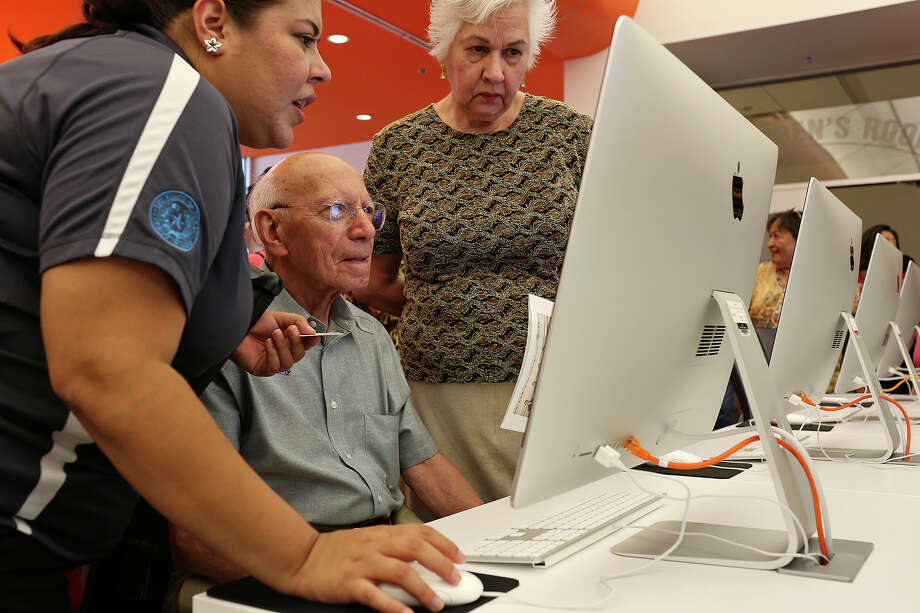 Maria Elena Martinez, Library Technical Assistant, left, helps Heron Pena, with his wife, Alice Yturri Pena, figure out his password to use his library card during the grand opening of BiblioTech, the first Bexar County Digital Library, in San Antonio on Saturday, September 14, 2013. Photo: Lisa Krantz, San Antonio Express-News / San Antonio Express-News