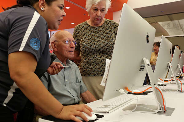 Maria Elena Martinez, Library Technical Assistant, left, helps Heron Pena, with his wife, Alice Yturri Pena, figure out his password to use his library card during the grand opening of BiblioTech, the first Bexar County Digital Library, in San Antonio on Saturday, September 14, 2013.