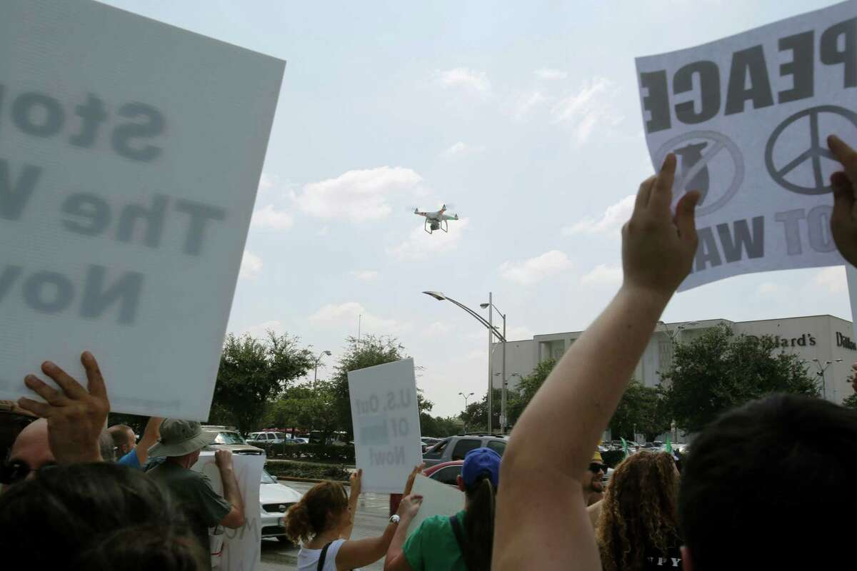 A camera-equipped drone floats above Houston crowds that were demonstrating either for or against U.S. involvement in the conflict in Syria last month.