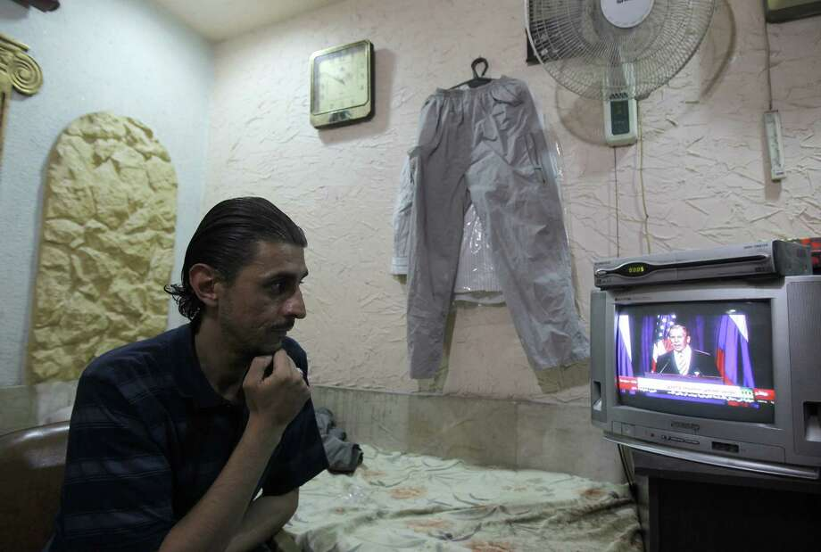 A Damascus merchant watches a news conference in which Secretary of State John Kerry and Russian counterpart Sergei Lavrov (on screen) announced a deal on Syria's chemical weapons. Photo: AFP / Getty Images