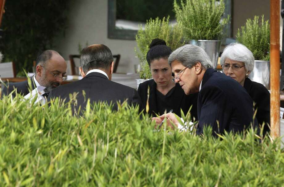 Secretary of State John Kerry (second right) and Russian Foreign Minister Sergey Lavrov (back to camera) talk with their senior aides in Geneva to negotiate the end of Syria's chemical weapons arsenal. Photo: Larry Downing / Associated Press