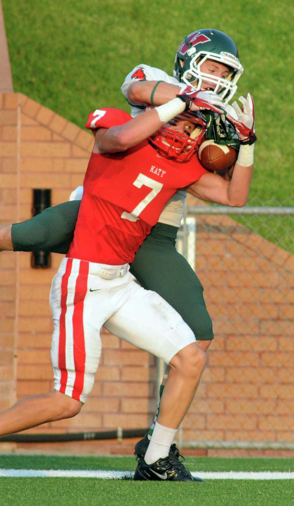 The Woodlands senior wide receiver Tyler Patrick, top, battles for possession of a deep pass with Katy junior defensive back Sy Slater during second action of their non-district matchup at Rhodes Stadium on Saturday.
