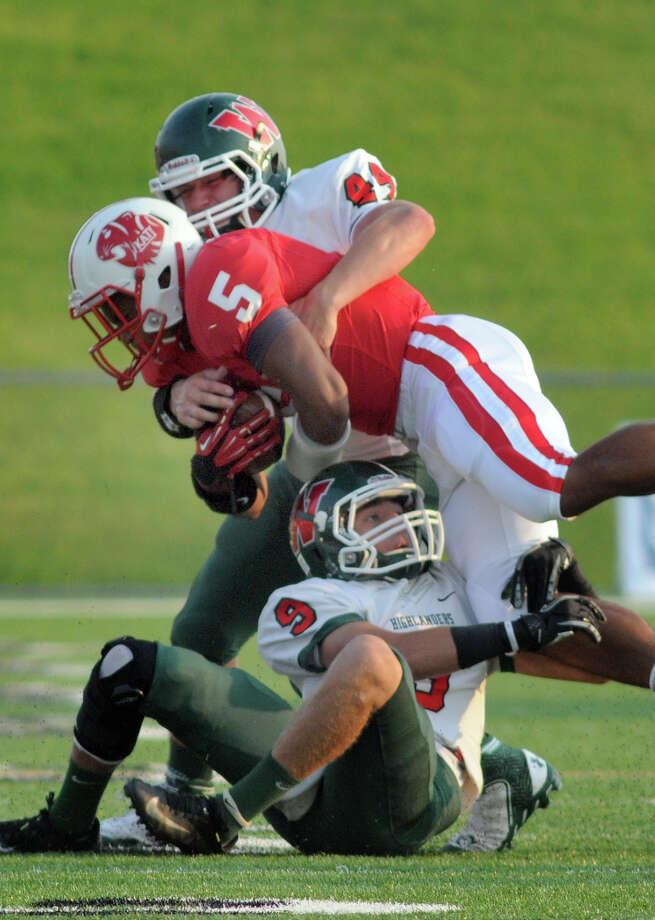 Katy sophomore running back Kyle Porter (#5) gets sandwiched by The Woodlands senior defensive back Tyler Murphy, bottom, and junior linebacker Tristan Horton, top, during first quarter action of their non-district matchup at Rhodes Stadium on Saturday. Photo: Jerry Baker, For The Chronicle