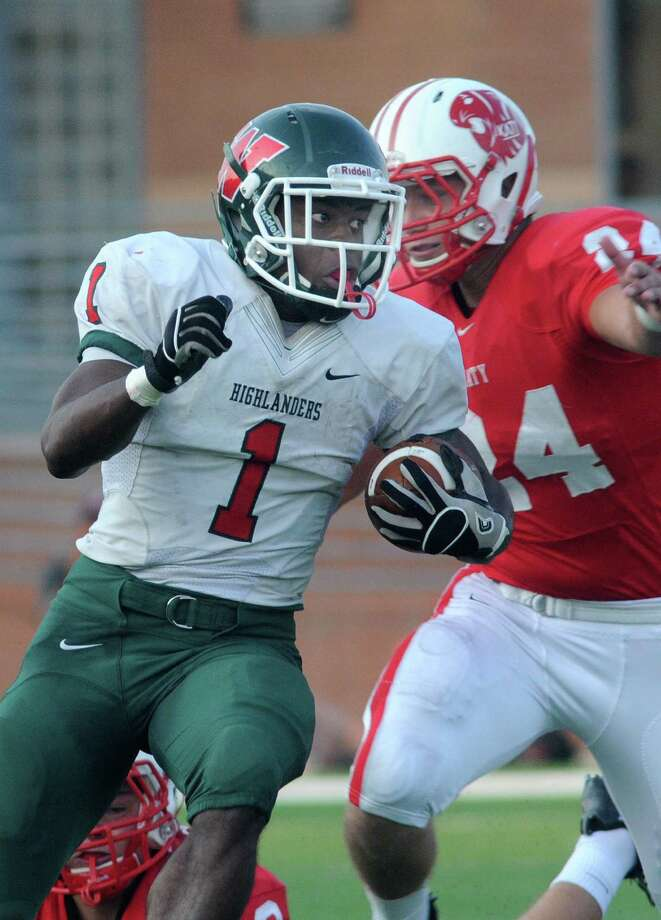 The Woodlands junior running back Patrick Carr (#1) works for yardage against Katy senior linebacker Jason Ellis during second quarter action of their non-district matchup at Rhodes Stadium on Saturday. Photo: Jerry Baker, For The Chronicle