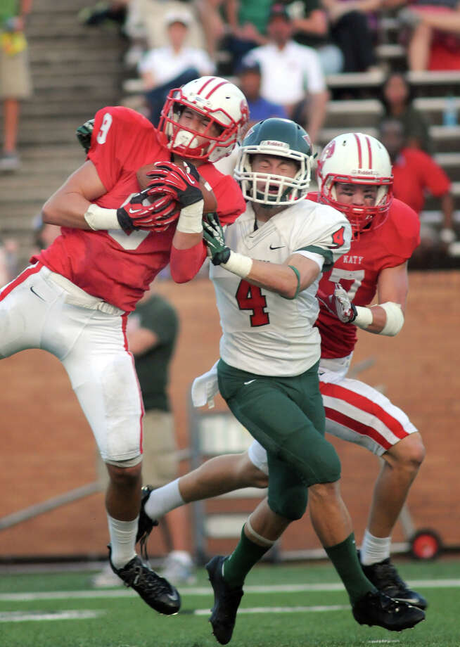 Katy sophomore defensive back Travis Whillock, left, backed up by junior  teammate Sy Slater, right, makes an interception on a pass intended for The Woodlands senior wide receiver Tyler Patrick during second quarter action of their non-district matchup at Rhodes Stadium on Saturday. Photo: Jerry Baker, For The Chronicle