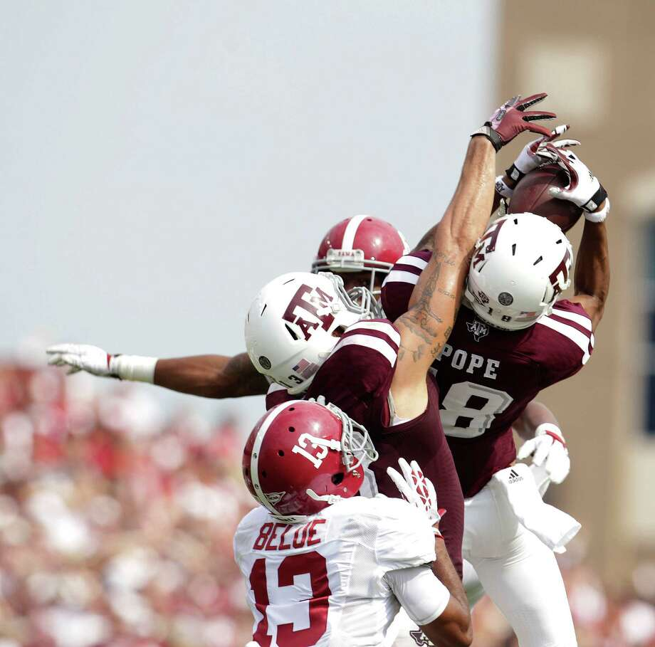After a lengthy scramble by Johnny Manziel, A&M receiver Edward Pope makes a leaping catch of a pass Manziel threw up for grabs. Photo: Karen Warren, Staff / © 2013 Houston Chronicle