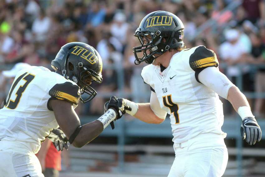 Texas Lutheran receiver Tyler Figol (4) is congratulated by teammate Deion Barnes after scoring a first-half touchdown against Trinity during college football action at Trinity University on Saturday, Sept. 14, 2013.