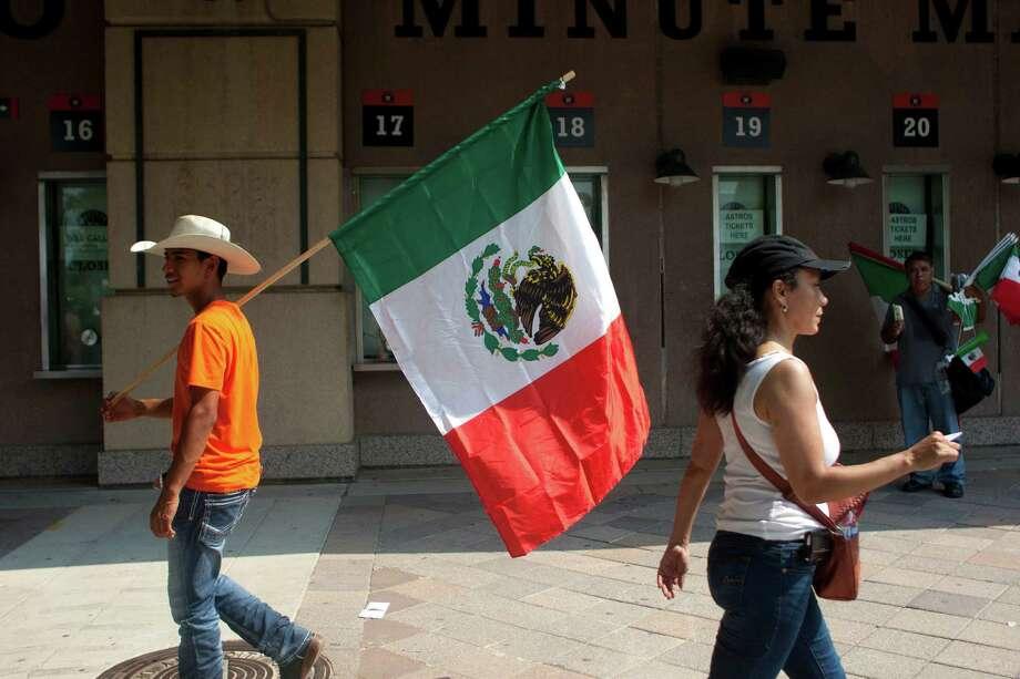 Jesus Buendia walks with a Mexican flag down Texas St. during the 45th annual Fiestas Patrias International Parade. Photo: Johnny Hanson, Houston Chronicle / Houston Chronicle