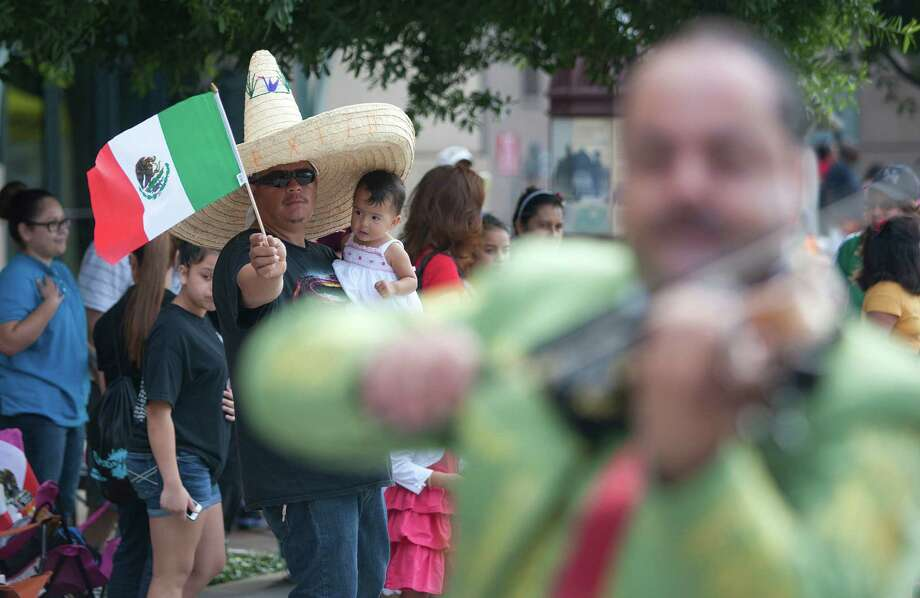 Marvin Dulce and his 11-month-old daughter, Ayala, watch the 45th annual Fiestas Patrias International Parade. Photo: Johnny Hanson, Houston Chronicle / Houston Chronicle