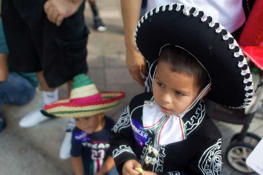 Jayden Chavez, 5, right, and his brother, Jacob, 3, watch as the 45th annual Fiestas Patrias International Parade made its way down Texas Street near Minute Maid Park. Photo: Johnny Hanson, Houston Chronicle / Houston Chronicle