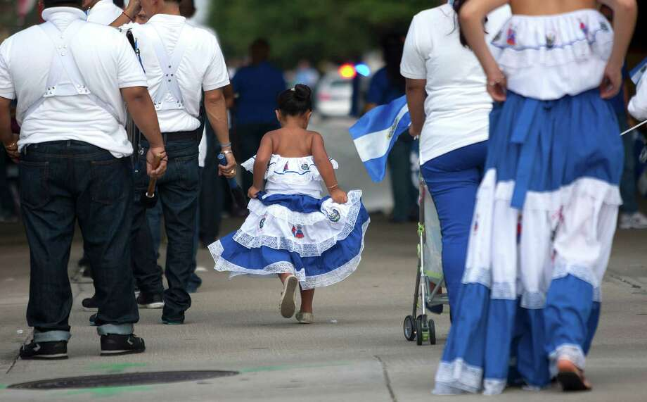 Hazel Cruz, 4, representing the country of El Salvador, runs to keep up with the group marching in the 45th annual Fiestas Patrias International Parade. Photo: Johnny Hanson, Houston Chronicle / Houston Chronicle