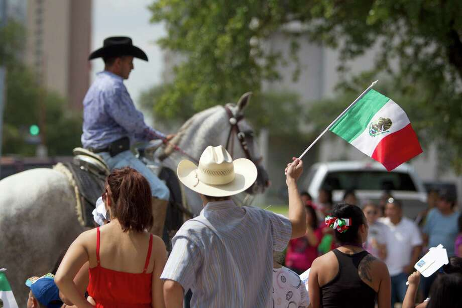 Leonel Rios waves a Mexican flag as he and his wife Yolanda, watched as the 45th annual Fiestas Patrias International Parade made its way down Texas Street near Minute Maid Park. Photo: Johnny Hanson, Houston Chronicle / Houston Chronicle