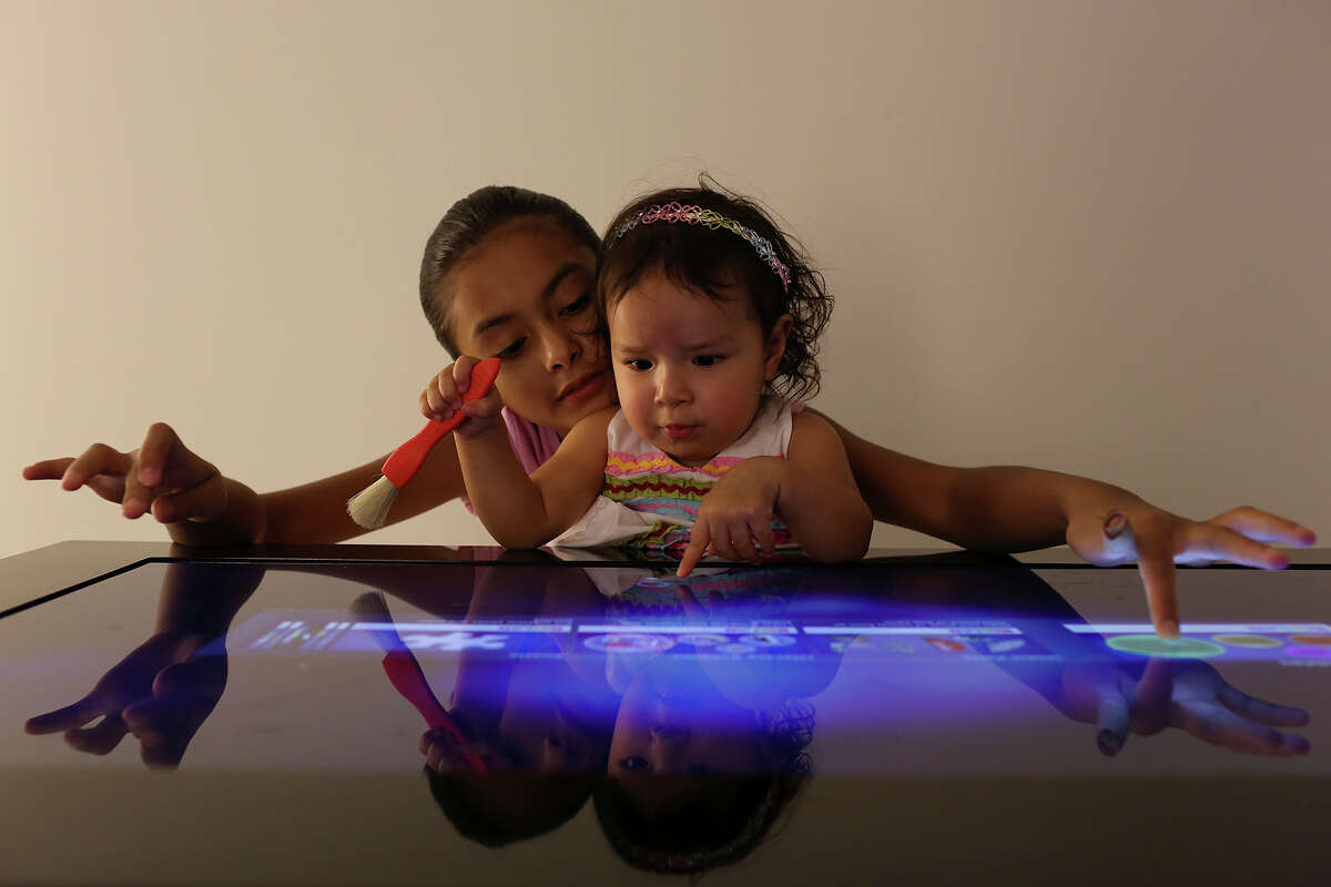 Belen Mendoza, 10, and her sister, Viviana Fierro, 1, play a Kaplan touch screen game during the grand opening of BiblioTech, the first Bexar County Digital Library, in San Antonio on Saturday, September 14, 2013.