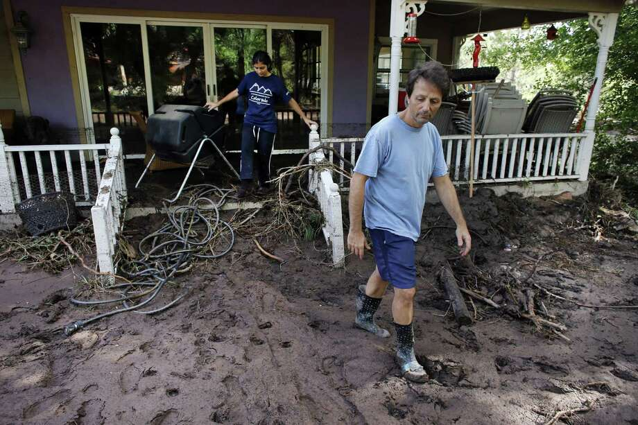 By air and by land, the rescue of hundreds of Coloradoans stranded by epic mountain flooding was accelerating as food and water supplies ran low. Allen Tawa, with his daughter Kayla, 17, examines what's left of their mud-clogged home on the southern edge of Boulder. Photo: Brennan Linsley / Associated Press