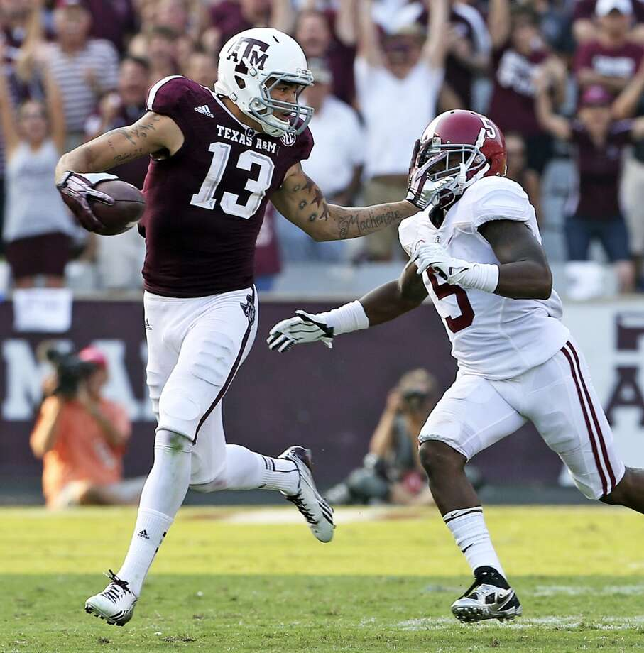 Mike Evans stiff arms after catching a pass and takeing it 95 yards for a touchdown against Cyrus Jones as  Texas A&M hosts Alabama at Kyle Field in College Station on September 14,  2013. Photo: TOM REEL