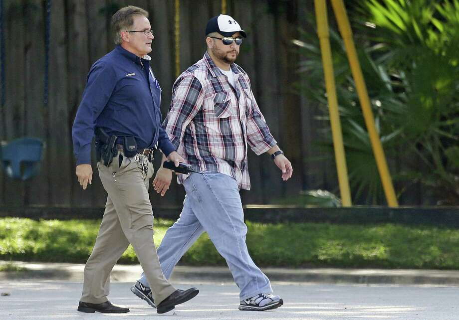 George Zimmerman (right) is escorted home Sept. 9 by a Lake Mary, Fla., police officer after a domestic incident in the neighborhood where Zimmerman and his wife had lived. Photo: John Raoux / Associated Press