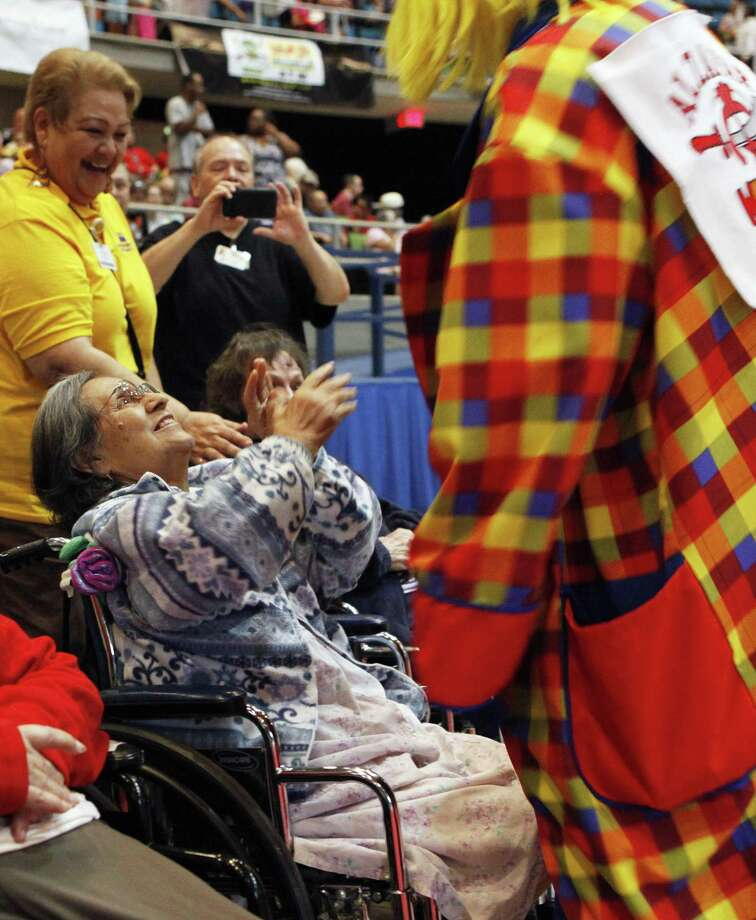 Rosario Corpus is delighted as a clown from the Alzafar Shrine Circus comes to hug her at Freeman Coliseum. Twenty-five residents of Morningside Ministries at Chandler Estate attended the circus, courtesy of the Alzafar Shriners. Photo: Cynthia Esparza / For The San Antonio Express-News