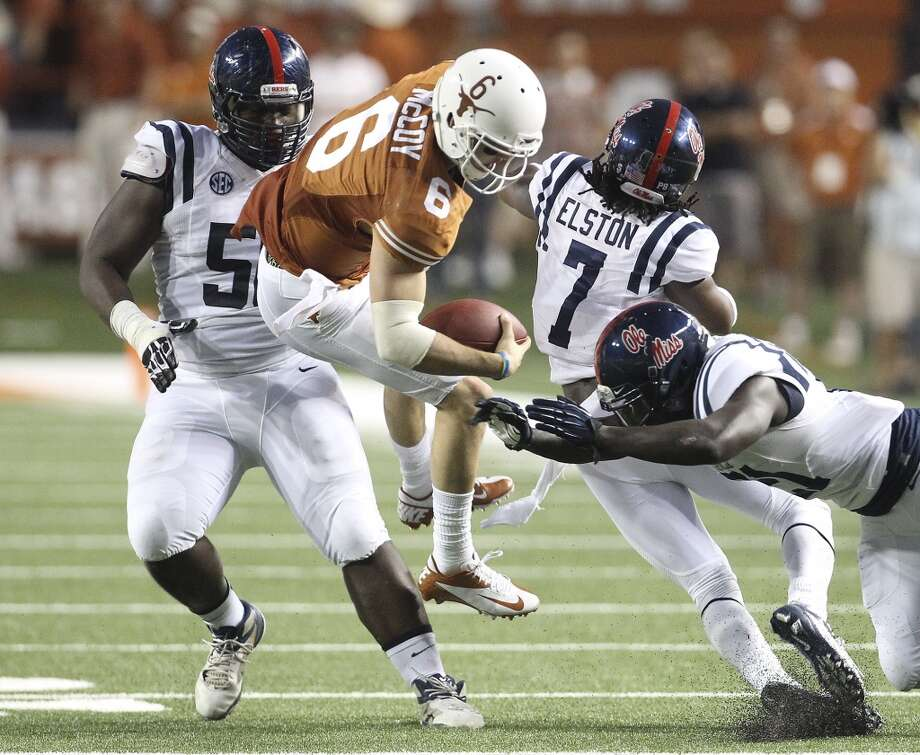 Texas quarterback Case McCoy (06) gets airborne while getting tackled by a trio of Ole Miss defenders Woodrow Hamilton (56), Trae Elston (07) and Senquez Golson (21) in the first half in Austin on Saturday, Sept. 14, 2013. (Kin Man Hui/San Antonio Express-News) Photo: Kin Man Hui, San Antonio Express-News