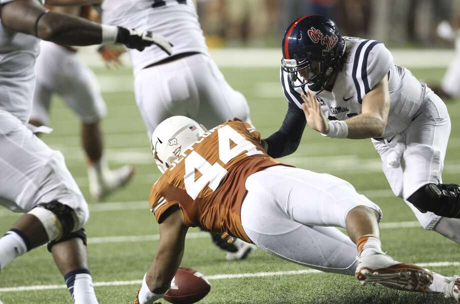 Texas' Jackson Jeffcoat (44) recovers a fumble by Ole Miss quarterback Bo Wallace (14) in the first half in Austin on Saturday, Sept. 14, 2013. (Kin Man Hui/San Antonio Express-News) Photo: San Antonio Express-News