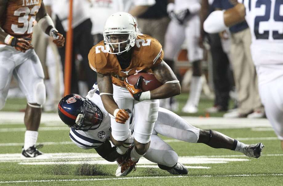 Texas receiver Kendall Sanders (02) gets tripped up by an Ole Miss defender in the first half in Austin on Saturday, Sept. 14, 2013. (Kin Man Hui/San Antonio Express-News) Photo: San Antonio Express-News