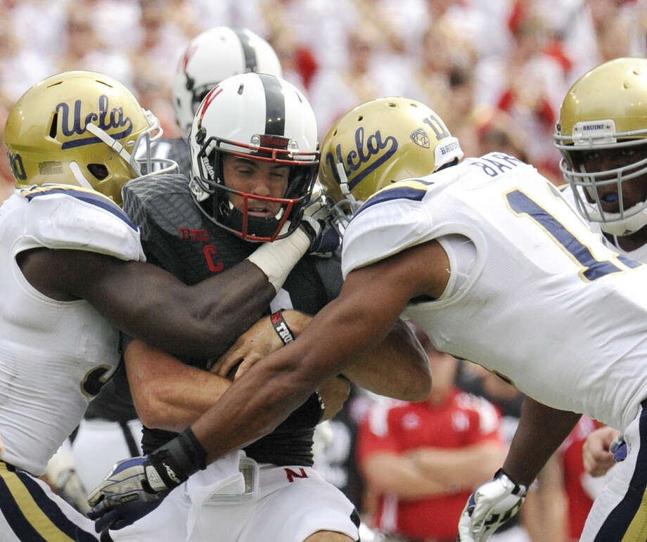 UCLA's Myles Jack (left) and Anthony Barr sandwich Nebraska quarterback Taylor Martinez in the third quarter of the Bruins' victory over the Cornhuskers. Photo: Francis Gardler / Associated Press