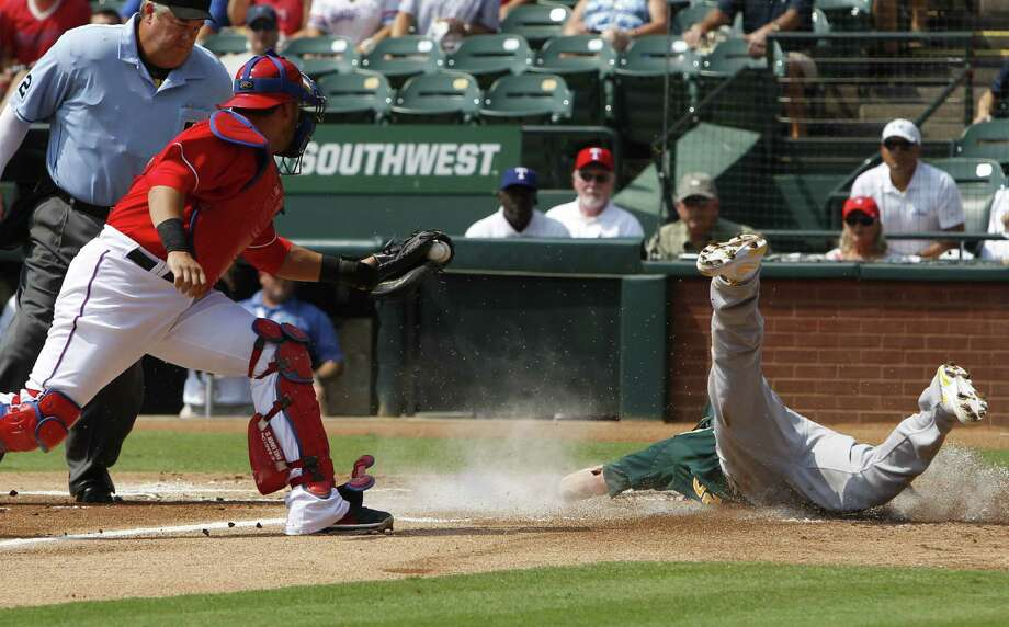 Rangers catcher Geovany Soto (left) gets the ball too late as Oakland's Josh Donaldson dives home. Photo: Richard Rodriguez / Fort Worth Star-Telegram