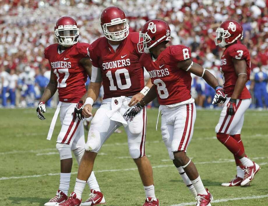 Oklahoma quarterback Blake Bell congratulates receiver Jalen Saunders (8) on his touchdown in the fourth quarter of a 51-20 over Tulsa. Photo: Sue Ogrocki / Associated Press