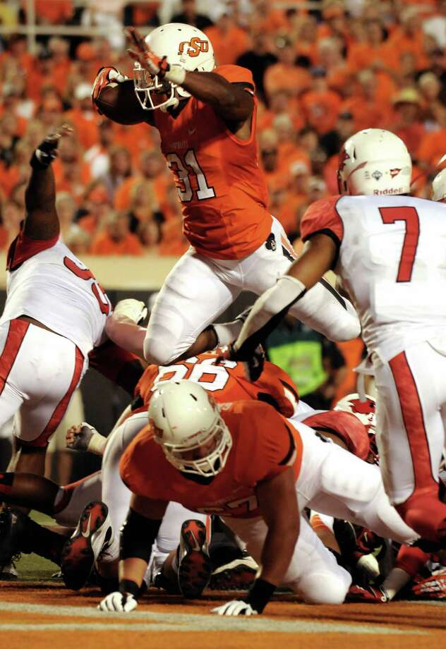 Oklahoma State running back Jeremy Smith, top center, jumps for a touchdown over the back of lineman Calvin Barnett, bottom, while Lamar defensive back Courtlin Thompson, right, watches during the first half of an NCAA college football game in Stillwater, Okla., Saturday, Sept. 14, 2012. (AP Photo/Brody Schmidt) Photo: Brody Schmidt, FRE / FR79308 AP