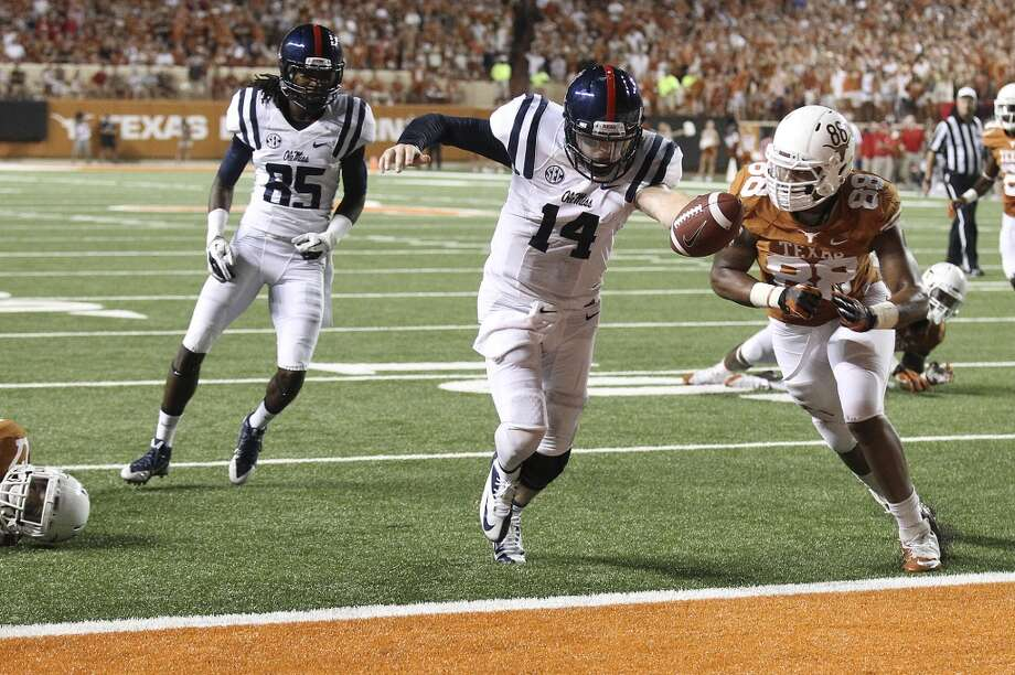 Ole Miss quarterback Bo Wallace (14) lunges for a touchdown against Texas' Cedric Reed (88) in the second half in Austin on Saturday, Sept. 14, 2013. Ole Miss defeats Texas, 44-23. (Kin Man Hui/San Antonio Express-News) Photo: Kin Man Hui, San Antonio Express-News