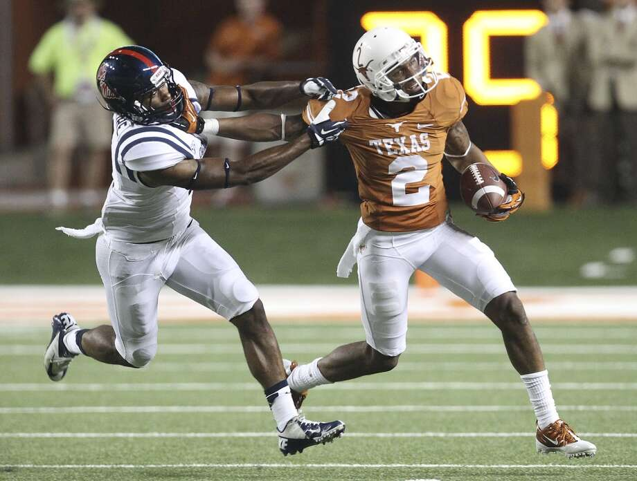 Texas' Kendall Sanders (02) tries to break the tackle of Ole Miss' Kailo Moore (04) on a kick return in the second half in Austin on Saturday, Sept. 14, 2013. Ole Miss defeats Texas, 44-23. (Kin Man Hui/San Antonio Express-News) Photo: Kin Man Hui, San Antonio Express-News