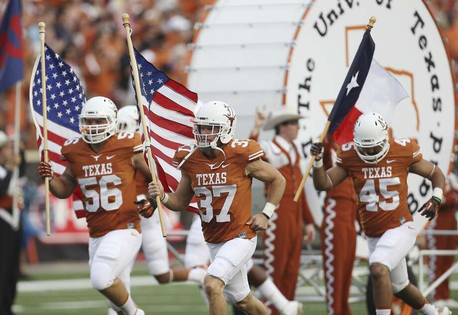 Texas' Nate Boyer (37) leads the team out with the U.S. Flag before the game against Ole Miss in the first half in Austin on Saturday, Sept. 14, 2013. (Kin Man Hui/San Antonio Express-News) Photo: Kin Man Hui, San Antonio Express-News