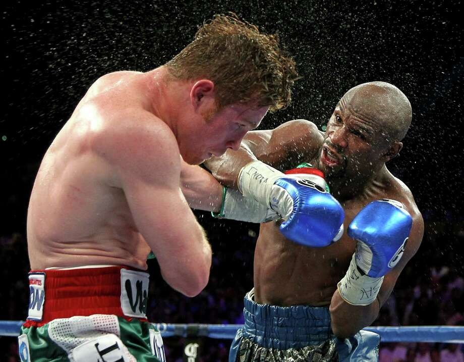 TOPSHOTS Boxers Floyd Mayweather Jr. of US (R) throws a left at Canelo Alvarez, Mexico, (L) during their WBC/WBA 154-pound title fight at the MGM Grand Garden Arena, September 14, 2013 in Las Vegas, Nevada. Mayweather won a majority decision.     AFP PHOTO / John GURZINSKIJOHN GURZINSKI/AFP/Getty Images Photo: JOHN GURZINSKI, AFP/Getty Images / AFP