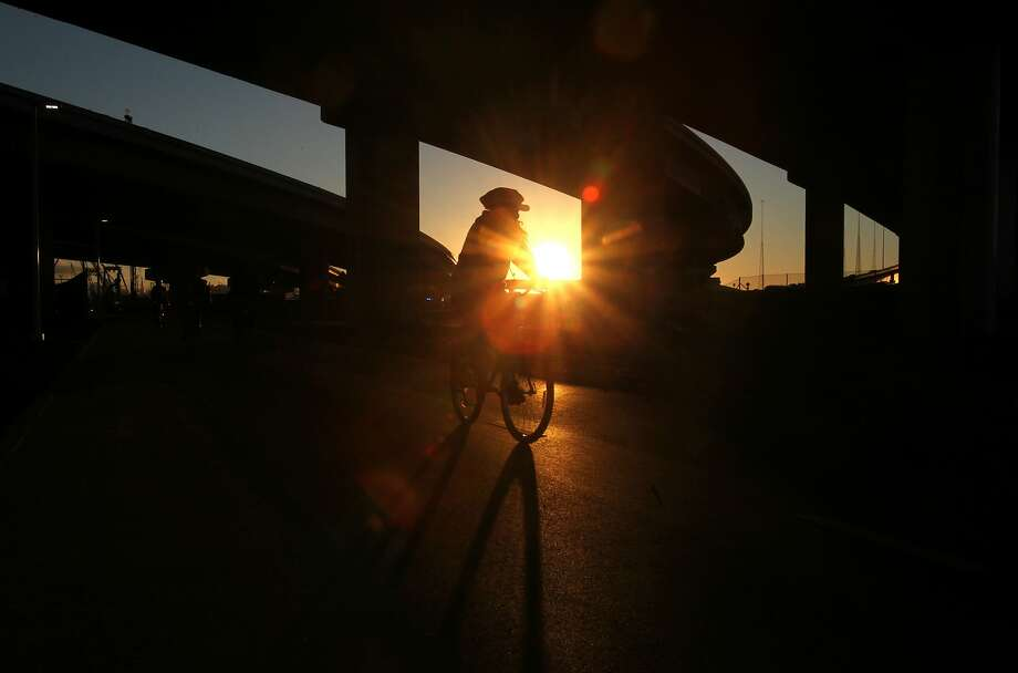 A cyclist rides under an over pass as the sun sets September 14, 2013 on the new Bay Bridge bike path in Oakland. Photo: Leah Millis, The Chronicle