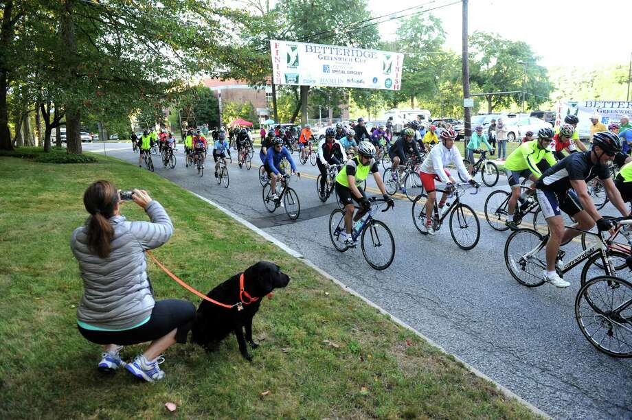 Liz Urdang, of Stamford, with Tikki, a Labrador retriever, takes photographs at the race at the 29th annual HSS Tour de Greenwich, hosted by Threads &  Treads, at Greenwich High School, in Greenwich, in Conn., Sunday, Sept. 15, 2013. Photo: Helen Neafsey / Greenwich Time