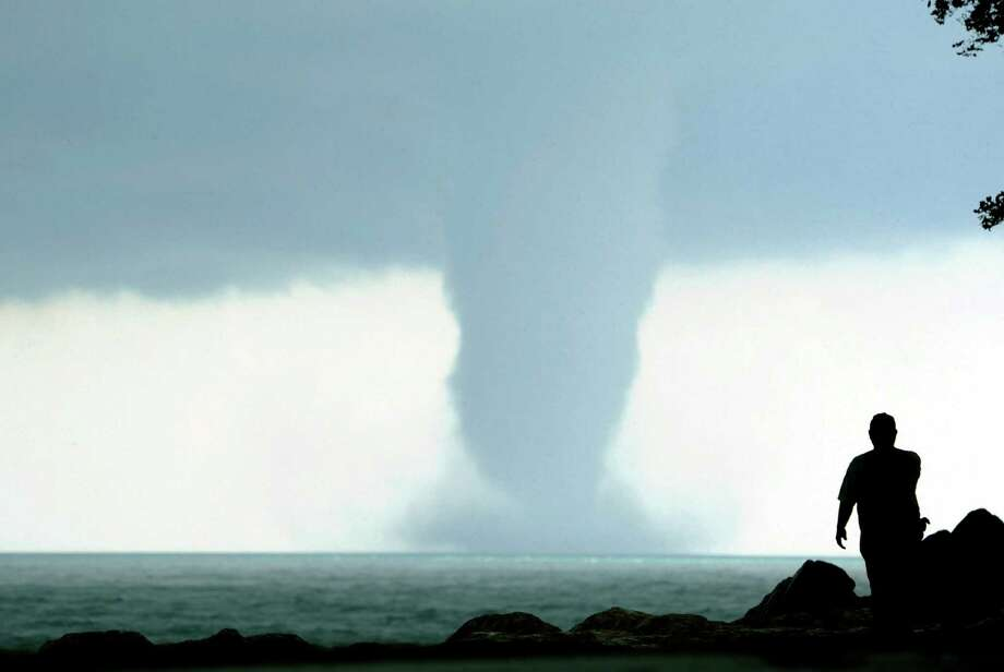 A person takes photos of a large water spout on Lake Michigan south east of Kenosha, Wis. on Thursday, Sept. 12, 2013. At times two separate spouts were visible as clouds rotated. The National Weather Service in Sullivan said the water spouts occurred about four miles southeast from Kenosha. A water spout is basically a tornado over water, meteorologist Ed Townsend said. Photo: AP