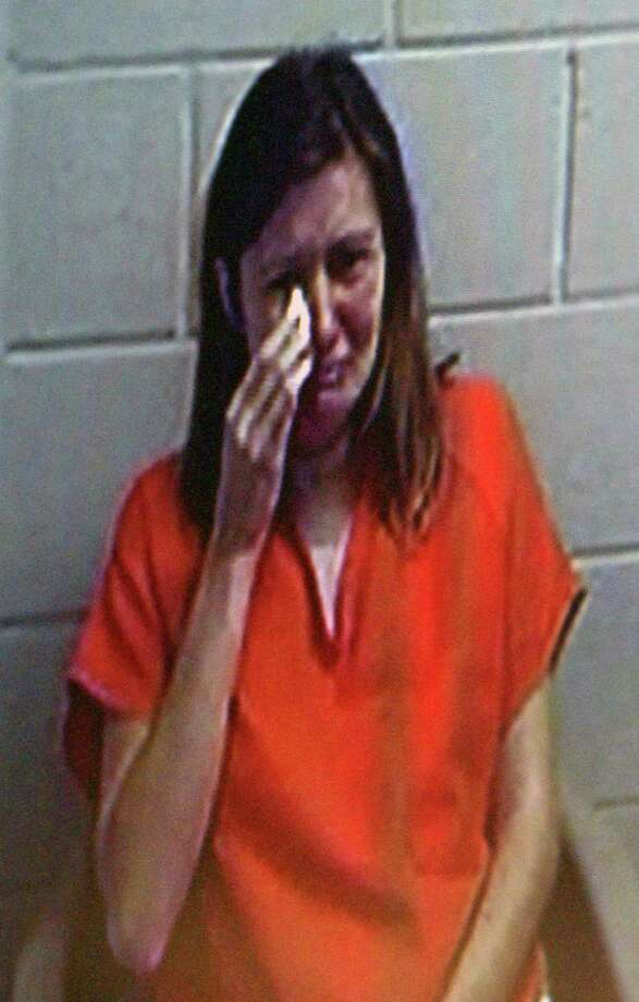 Sarah Knysz wipes her face as she is displayed on a video screen during her arraignment before Mason County's 79th District Court Magistrate Patricia Baker in Ludington, Mich. on Wednesday, Sept. 11, 2013. Sarah Knysz's husband Eric Knysz has been charged with murder of an officer as well as three other crimes in the shooting of a state trooper. Sarah Knysz faces two charges related to driving away from the scene with him. Photo: AP