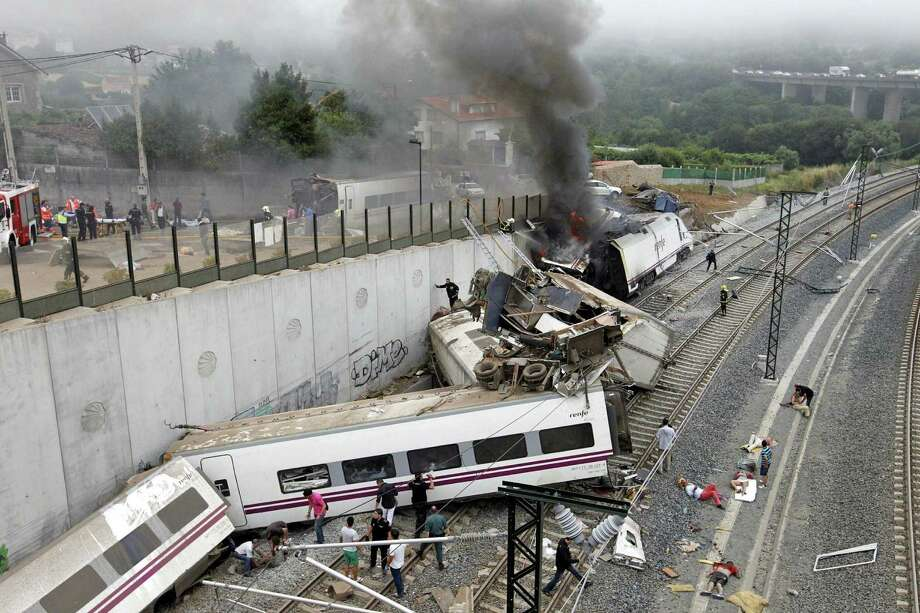 FILE - In this July 24, 2013 file photo, emergency personnel respond to the scene of a train derailment in Santiago de Compostela, Spain. The judge investigating a high-speed train crash that killed 79 people in Spain wants to question senior officials of the country's rail infrastructure company, Adif about track safety. A court statement published Tuesday, Sept. 10, 2013 said they, and potentially others from Adif, will be questioned as suspects as the judge tries to determine whether the track was safe. Photo: AP