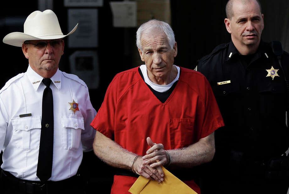 FILE - In this Oct. 9, 2012 file photo, former Penn State University assistant football coach Jerry Sandusky, center, is taken from the Centre County Courthouse by Centre County Sheriff Denny Nau, left, and a deputy, after being sentenced in Bellefonte, Pa.   Sandusky's challenge to his child molestation conviction goes before a state appeals court on Tuesday, Sept. 17, 2013, as the former Penn State assistant football coach seeks to overturn a sentence that could keep him behind bars for life. Photo: AP